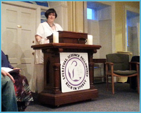 Image of Rev. Eileen Casey Gonzalez standing at Spiritual Science Fellowship Platform. She is speaking at the platform.