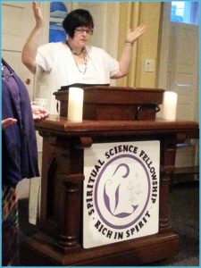 Image of Eileen Casey Gonzalez leading a service of the Spiritual Science Fellowship. She has dark hair and is wearing white. She is standing at a podium with her hands in the air while giving a prayer.
