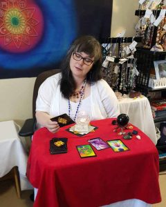Image of Clairvoyant Medium Eileen Casey Gonzalez sitting at a table doing a mediumship reading. She is wearing white, she has long dark hair and is holding an oracle card in her hand which she is looking at. She is sitting at a table with a red table cloth on it with reading cards, crystals, and a glass of water with a candle which she uses to see clairvoyant visions.