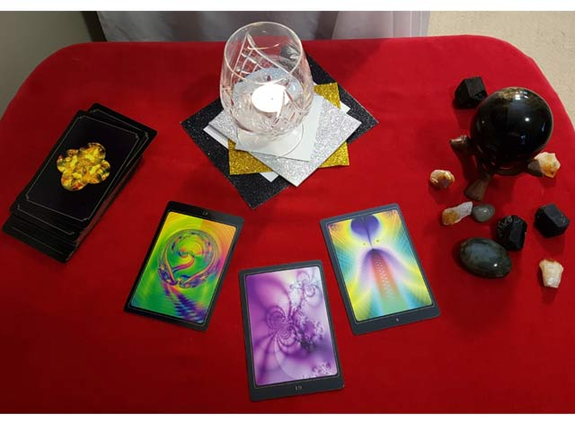 Image of tools a Psychic or Clairvoyant Medium may use. It includes oracle cards, a glass with a candle lit inside of it, a black crystal ball, and some crystals all placed on a table with a red cloth.