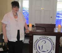 Image of Rev. Eileen Casey Gonzalez standing at the podium of the Spiritual Science Fellowship in Halifax. She has her dark hair tied up on her head, is wearing a white shirt and a minister's stoll.